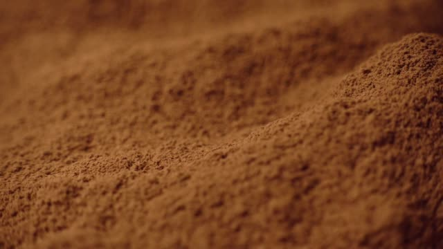 Shot of cocoa powder being sifted through a small handheld sift and rotating, 4K