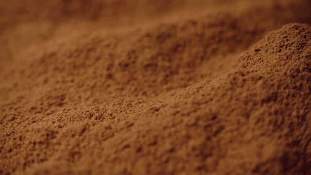 vídeos de stock e filmes b-roll de shot of cocoa powder being sifted through a small handheld sift and rotating, 4k - cacau em pó
