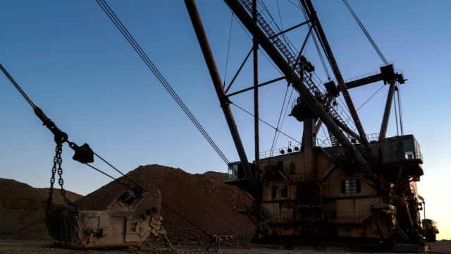 PAN shot of dragline Super heavy excavator standing on the side of the quarry against sunset on the blue sky. video