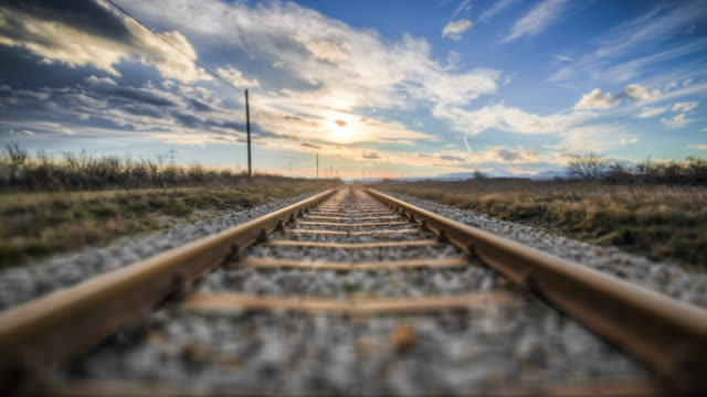 POV shot of emtpy railroad tracks in a desert sunny landscape