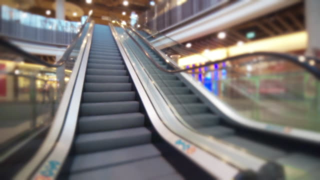 LS shot of Escalator upstairs. LS Hand-held Camera and selective focus with color grading. Use for background clip or insert shot of Escalator upstairs. shopping mall stock videos & royalty-free footage