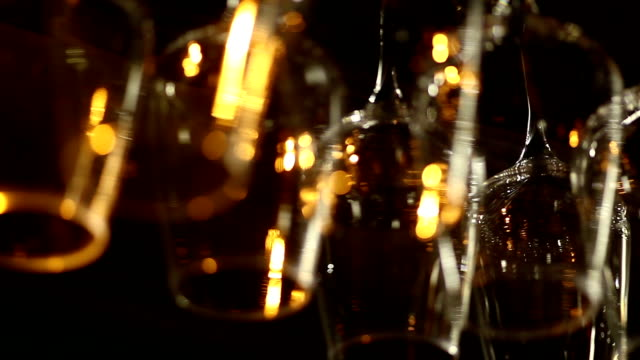 shot of glasses hanging in a bar - bicchiere vuoto video stock e b–roll