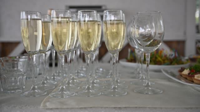 vidéos et rushes de tiré de verres de champagne alignés en rangées sur une table d'attente pour les invités de réception de mariage - flûte à champagne