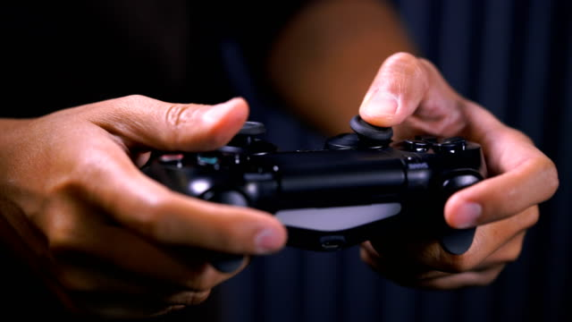 ECU Shot of hands holding video game console controlling joystick