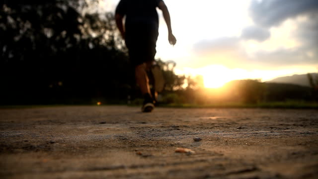Shot of male running at sunset. - vídeo