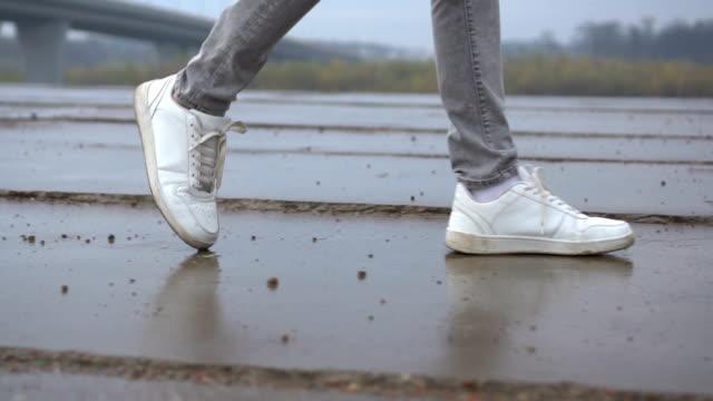 タイルの道を歩いているスニーカーの男性の足のショット。都市環境 - ステップ点の映像素材/bロール