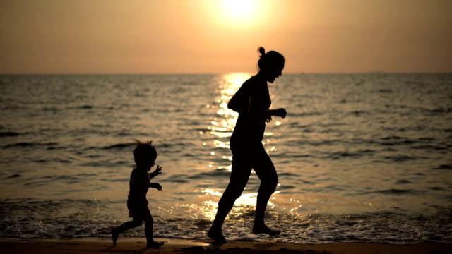 2 skott av mor och baby pojke jogga på stranden. - pattaya bildbanksvideor och videomaterial från bakom kulisserna