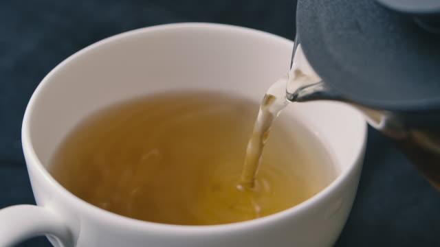 カップファインダイニングアフタヌーンティーに紅茶を注ぐSLO MOショット ビデオ