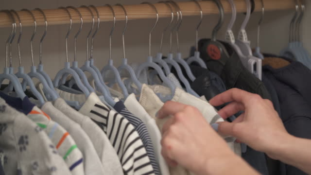a shot of racks with baby's clothes. woman's hand start sorting them out - abbigliamento da neonato video stock e b–roll