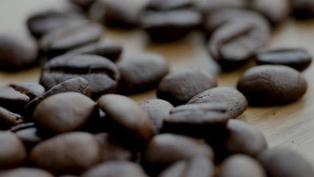 vídeos de stock e filmes b-roll de shot of  roasted coffee bean on the floor - bebida com espuma