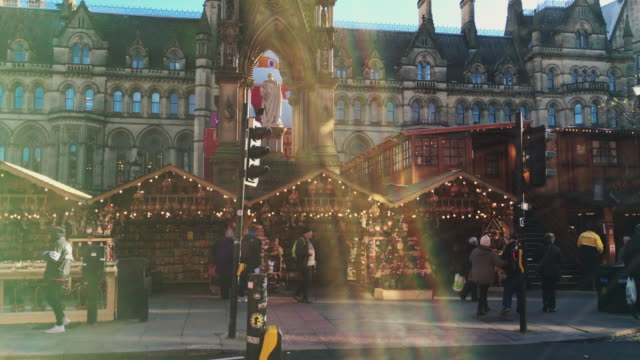 MANCHESTER,UK - DECEMBER 16, 2016. Shot of shoppers at the Christmas market in front of the Manchester Town Hall on Albert Square. December 16, 2016 video