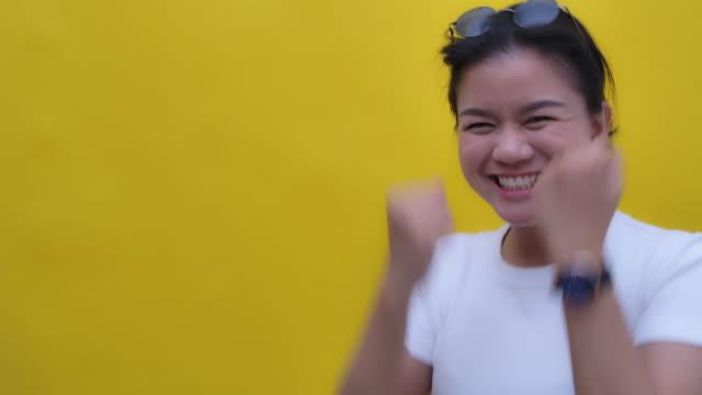 白いブラウスと白い sunhat とサングラスを身に着けているはい手のジェスチャーで笑顔の幸せな女性の遅いモーメントショット ビデオ