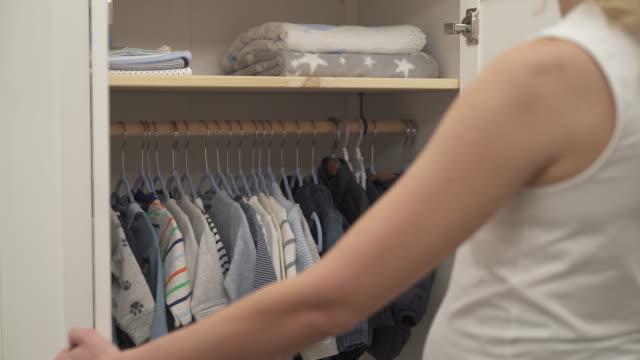 ett skott av sluten vit garderob. en blond kvinna närmar sig den. hennes händer öppna dörrarna. i området i närheten finns det barnets kläder. - looking inside inside cabinet bildbanksvideor och videomaterial från bakom kulisserna