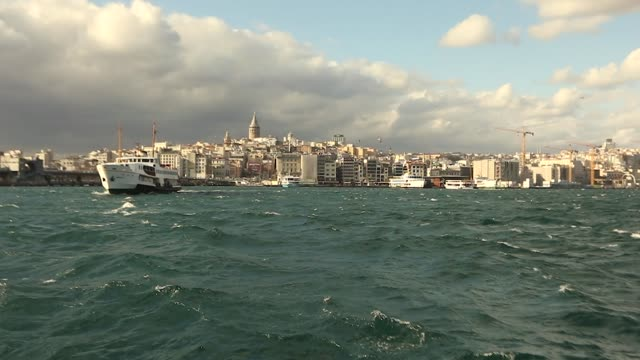 Shot of the Galata Tower, in the foreground pleasure boats with tourists and seagulls. Pleasure boats on the background of the Galata Tower, windy weather