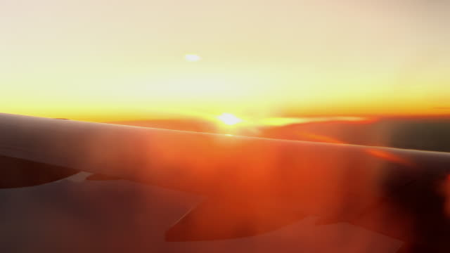 Shot of the Horizon at Sunset from Over the Wing of a Commercial Airliner Jet