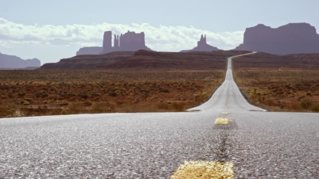 Shot of the Middle of a Highway/Interstate in the Desert of Arizona on a Bright, Sunny Day with Mountains and Rock Formations in the Distance
