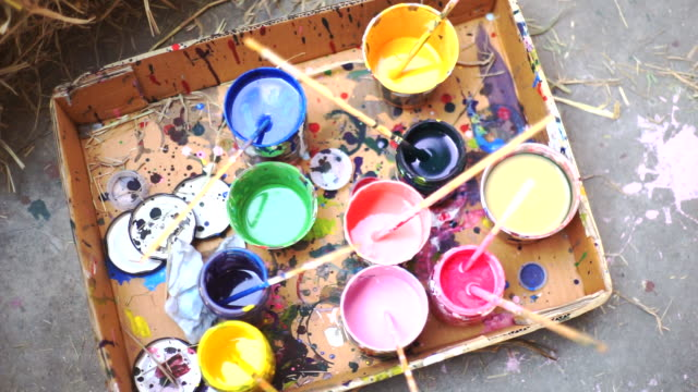 2 shot of Top view of multicolored paint cups with paint brushes in cups, DIY art and craft accessory.