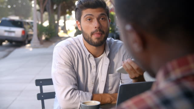 Shot of two male friends with coffees outside coffee shop video