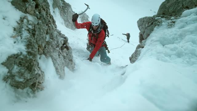 ld aufnahme von winter bergsteiger klettern bei widrigen verhältnissen - eisklettern stock-videos und b-roll-filmmaterial