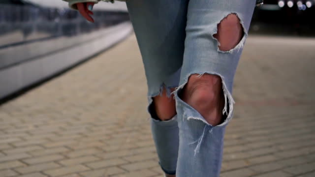 shot of woman legs in ripped jeans walking on tile road. urban environment - jeans video stock e b–roll