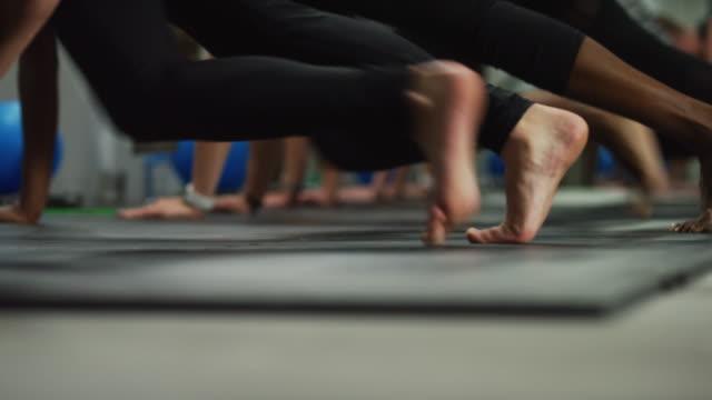 colpo di piedi e gambe delle donne che eseguono esercizi di alpinisti sul pavimento in palestra - metodo pilates video stock e b–roll