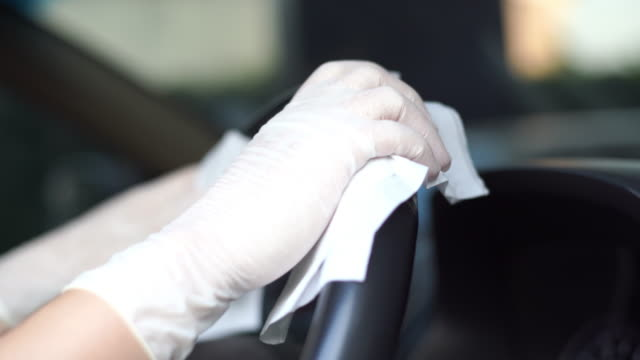 CU shot of Women's Hand in Glove wiping down steering wheel. 4K Video by CU Hand-held Camera and selective focus with color grading. Use for background clip or insert shot of Women's Hand in Glove wiping down steering wheel. cleaning stock videos & royalty-free footage