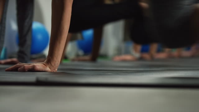 colpo di mani, braccia e gambe delle donne che eseguono esercizi di alpinisti sul pavimento in palestra - metodo pilates video stock e b–roll