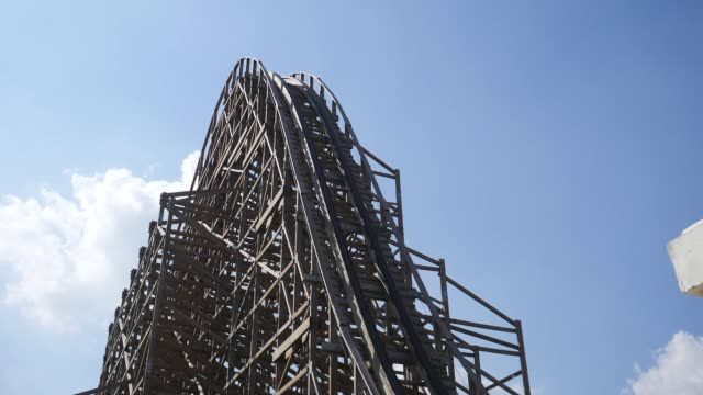 shot of wooden roller coaster with blue sky at background - roller coaster stock videos & royalty-free footage