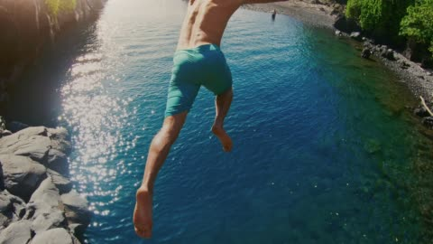 vidéos et rushes de pov tourné de jeune homme aventureux sautant dans la belle piscine de l'océan - vacances