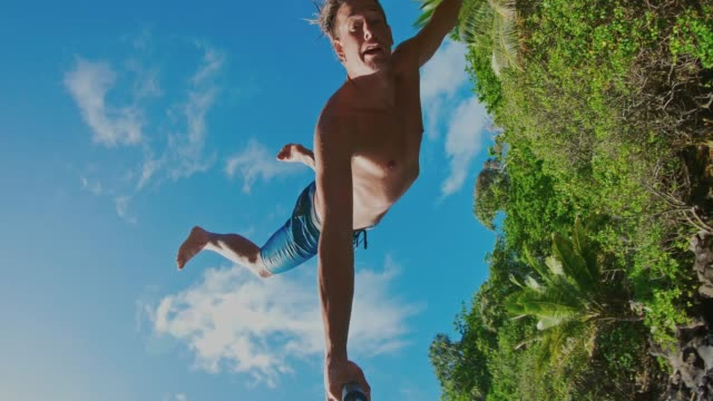 pov shot of young man cliff jumping - adrenalina video stock e b–roll