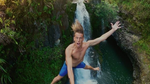 pov 拍攝的年輕人懸崖跳躍與瀑布 - 懸崖 個影片檔及 b 捲影像