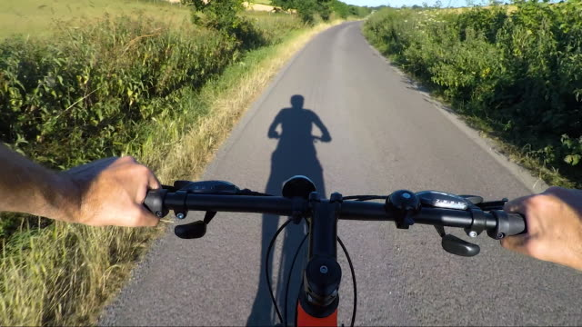 POV shot on bicycle ride along country road Action camera shot. biking stock videos & royalty-free footage