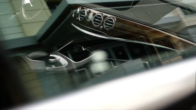 A shot through the glass of a wooden dashboard of an expensive car A shot through the glass of a wooden dashboard of an expensive business class car. luxury car stock videos & royalty-free footage