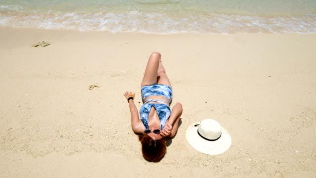 4k shots : a woman sunbathes on the beautiful beach of thailand - opalenizna filmów i materiałów b-roll