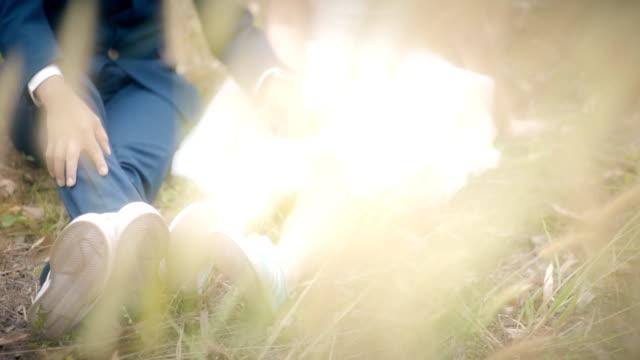 2 ショットのカップルのリラクゼーションと黄金の草原の前景草のフィールドで休憩します。結婚式のテーマ。 - ウェディングファッション点の映像素材/bロール