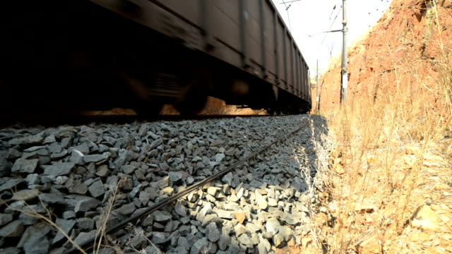 Shots from different angles, next to a rail line, of a train going past and into a tunnel video