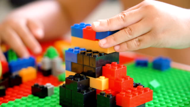 cs 2 shots of boy hand playing plastic blocks. - giocattolo video stock e b–roll