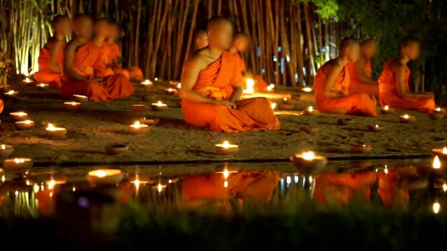 vídeos y material grabado en eventos de stock de 2 tiros del budismo, novicios budistas están meditando en día asalha puja por la noche - hermano