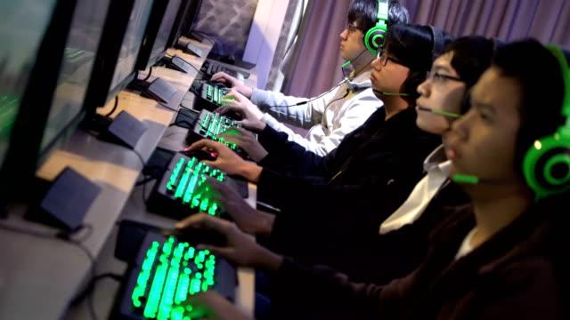 2 shots of four gamers team in a row at computer game cafe - współzawodnictwo wydarzenia filmów i materiałów b-roll
