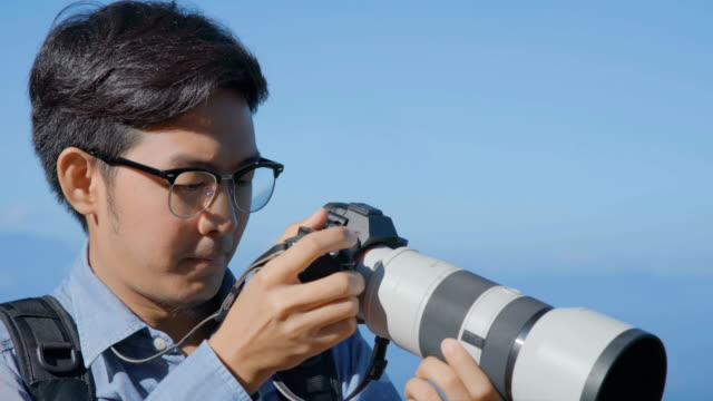 2 shots of Male Professional Photographer using Camera with Long Lens to taking photos video