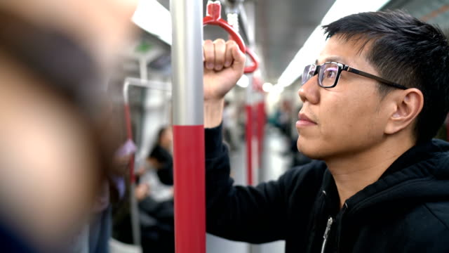 2 shots of man holding handrail or hand grip straps in subway - parapetto barriera video stock e b–roll