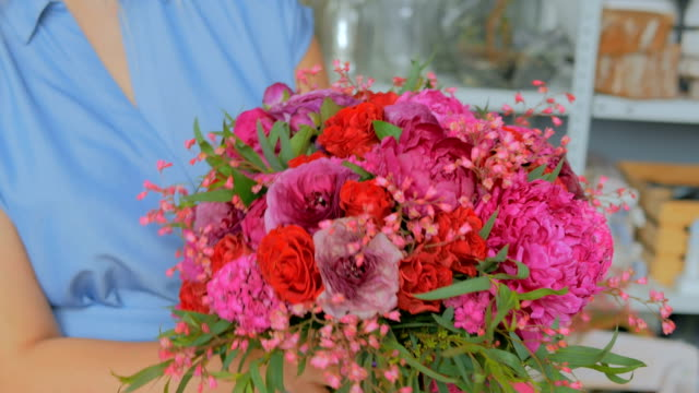 3 shots. Professional florist holding and checking bouquet at studio video