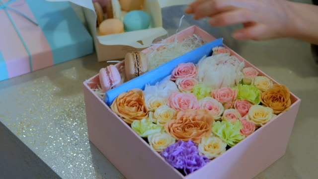 2 shots. Professional florist making gift box with flowers and cake macarons at flower shop video