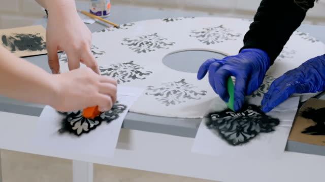 4 shots. Two women decorators, designers painting wooden circle decoration video
