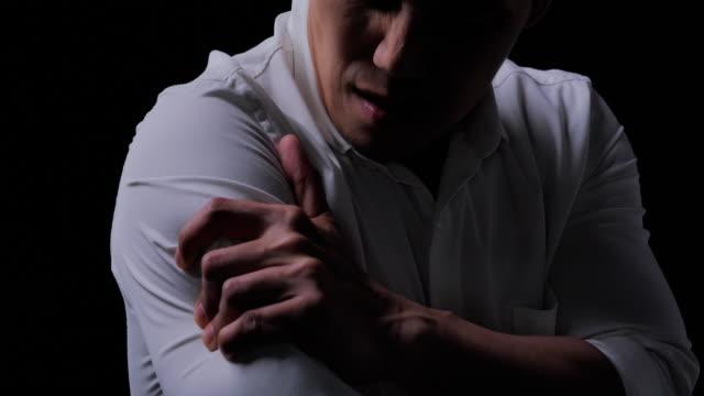 어깨 부상, 어깨에 통증이젊은 남자, 검은 배경에 인체에 통증. 사무실 증후군, 라이프 스타일, 건강 관리, 의료, 사람들 개념. 집에서 아픈 - 몸매 관심 스톡 비디오 및 b-롤 화면