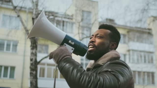 stockvideo's en b-roll-footage met schreeuw megaphone. zwarte levens materie. rebel in crowd demonstranten. politieke staking - megafoon