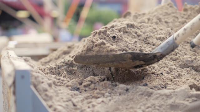 Shovel digging sand from large pile close up