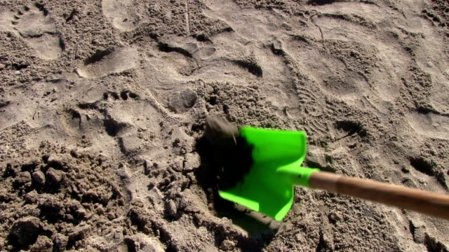 Shoveling sand with green shovel closeup video