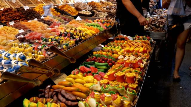 vídeos de stock, filmes e b-roll de vitrine de doces coloridos no mercado la boqueria. barcelona, espanha - estilo de vida dos abastados