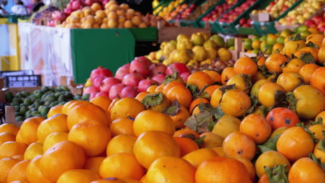 vídeos de stock e filmes b-roll de showcase with various fruits, persimmons, tangerines, pears and more in the street market - diospiro